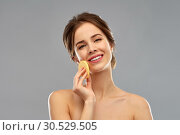 Купить «young woman cleaning face with exfoliating sponge», фото № 30529505, снято 20 января 2019 г. (c) Syda Productions / Фотобанк Лори