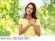 Купить «smiling teenage girl holding hands on heart», фото № 30529561, снято 29 января 2019 г. (c) Syda Productions / Фотобанк Лори