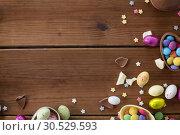 Купить «chocolate eggs and candy drops on wooden table», фото № 30529593, снято 22 марта 2018 г. (c) Syda Productions / Фотобанк Лори
