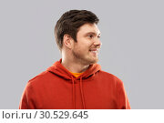 smiling young man in red hoodie over grey. Стоковое фото, фотограф Syda Productions / Фотобанк Лори