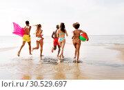 Купить «friends run with beach ball and swimming mattress», фото № 30529697, снято 29 июля 2018 г. (c) Syda Productions / Фотобанк Лори