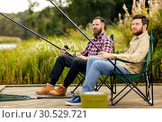 Купить «friends with fishing rods at lake or river», фото № 30529721, снято 8 сентября 2018 г. (c) Syda Productions / Фотобанк Лори