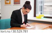 Купить «Business concept. A woman in glasses sit by the table and fills the documents», фото № 30529781, снято 6 декабря 2019 г. (c) Константин Шишкин / Фотобанк Лори