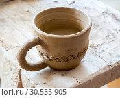 Купить «Глиняная чашка, только что изготовленная мастером», фото № 30535905, снято 22 августа 2018 г. (c) Вячеслав Палес / Фотобанк Лори