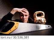 Купить «Man with saw and heavy weight of gold», фото № 30536381, снято 14 февраля 2011 г. (c) Tryapitsyn Sergiy / Фотобанк Лори