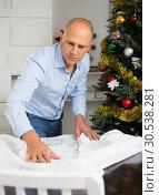 Купить «Man spreading tablecloth on table», фото № 30538281, снято 10 января 2019 г. (c) Яков Филимонов / Фотобанк Лори
