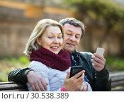 Купить «Mature couple with smartphones outdoors», фото № 30538389, снято 23 августа 2019 г. (c) Яков Филимонов / Фотобанк Лори
