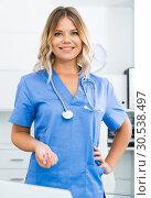 Купить «Friendly girl in doctor's uniform smiling at office», фото № 30538497, снято 17 октября 2017 г. (c) Яков Филимонов / Фотобанк Лори