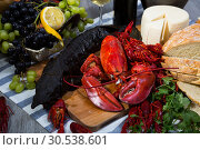 Smoked sturgeon with lobster, crayfishes, bread, cheese, fruits and wine. Стоковое фото, фотограф Яков Филимонов / Фотобанк Лори