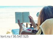 Купить «Woman reading a book at the beach», фото № 30547525, снято 22 декабря 2013 г. (c) Tryapitsyn Sergiy / Фотобанк Лори