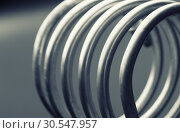 Купить «Aluminum spiral isolated on gray background», фото № 30547957, снято 10 апреля 2014 г. (c) Tryapitsyn Sergiy / Фотобанк Лори