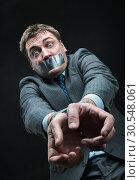 Купить «Man with mouth covered by masking tape», фото № 30548061, снято 21 апреля 2014 г. (c) Tryapitsyn Sergiy / Фотобанк Лори