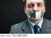 Купить «Man with mouth covered by masking tape», фото № 30548065, снято 21 апреля 2014 г. (c) Tryapitsyn Sergiy / Фотобанк Лори