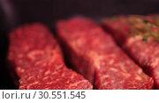 Купить «pieces tenderloin of fresh raw marble beef meat with rosemary are lying in black tray ready for sale in slow mo camera motion 4K video with no people», видеоролик № 30551545, снято 5 ноября 2018 г. (c) Uladzimir Sitkouski / Фотобанк Лори