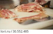 Купить «Man or woman butcher hands are laying out the bacon bits on the store shelf for sale in slow mo close up 4K video», видеоролик № 30552485, снято 5 ноября 2018 г. (c) Uladzimir Sitkouski / Фотобанк Лори
