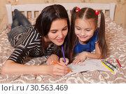 Купить «Little girl and mother draw lying on a bed.», фото № 30563469, снято 24 ноября 2016 г. (c) Tryapitsyn Sergiy / Фотобанк Лори