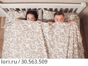 Young couple peeping from bedsheet at bedroom. Стоковое фото, фотограф Tryapitsyn Sergiy / Фотобанк Лори