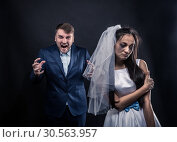 Bride with tearful face and terrible brutal groom. Стоковое фото, фотограф Tryapitsyn Sergiy / Фотобанк Лори