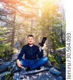 Smiling photographer with camera in yoga pose. Стоковое фото, фотограф Tryapitsyn Sergiy / Фотобанк Лори