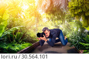 Male squat, photographing green nature on camera. Стоковое фото, фотограф Tryapitsyn Sergiy / Фотобанк Лори