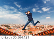 Male photographer jumping on the roofs of houses. Стоковое фото, фотограф Tryapitsyn Sergiy / Фотобанк Лори