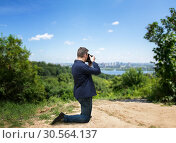 Male photographer taking picture of cityscape. Стоковое фото, фотограф Tryapitsyn Sergiy / Фотобанк Лори