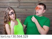 Купить «Playful couple with funny glasses on a sticks», фото № 30564329, снято 22 декабря 2016 г. (c) Tryapitsyn Sergiy / Фотобанк Лори