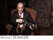 Купить «Contract killer holds automatic weapon», фото № 30564645, снято 19 января 2017 г. (c) Tryapitsyn Sergiy / Фотобанк Лори