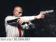 Купить «Bald hired killer in red tie aims a pistols», фото № 30564681, снято 19 января 2017 г. (c) Tryapitsyn Sergiy / Фотобанк Лори
