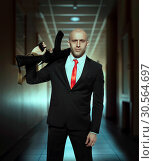 Купить «Murderer in suit and red tie holding machine gun», фото № 30564697, снято 19 января 2017 г. (c) Tryapitsyn Sergiy / Фотобанк Лори