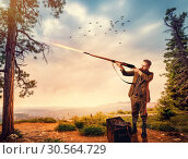 Duck hunter in hunting clothing aims an old rifle. Стоковое фото, фотограф Tryapitsyn Sergiy / Фотобанк Лори