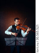 Купить «Male violinist playing classical music on violin», фото № 30565521, снято 4 марта 2017 г. (c) Tryapitsyn Sergiy / Фотобанк Лори