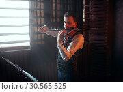 Купить «Male violinist playing on violin against window», фото № 30565525, снято 4 марта 2017 г. (c) Tryapitsyn Sergiy / Фотобанк Лори