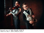 Saxophonist and violinst playing classical melody. Стоковое фото, фотограф Tryapitsyn Sergiy / Фотобанк Лори
