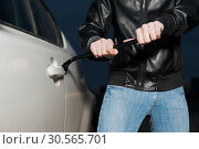 Купить «Male car thief open door with jemmy», фото № 30565701, снято 17 марта 2017 г. (c) Tryapitsyn Sergiy / Фотобанк Лори