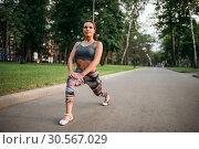 Купить «Athletic woman exercises, fitness training in park», фото № 30567029, снято 6 июня 2017 г. (c) Tryapitsyn Sergiy / Фотобанк Лори