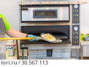 Купить «Baker hands with shovel, cooking pizza», фото № 30567113, снято 4 июня 2017 г. (c) Tryapitsyn Sergiy / Фотобанк Лори