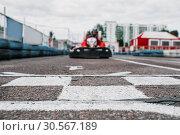 Купить «Karting racer on finish line, go kart competition», фото № 30567189, снято 15 июня 2017 г. (c) Tryapitsyn Sergiy / Фотобанк Лори