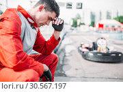 Купить «Karting racer sits on a tire, outdoor kart track», фото № 30567197, снято 15 июня 2017 г. (c) Tryapitsyn Sergiy / Фотобанк Лори