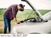 Купить «Tired man tries to repair a broken car», фото № 30567397, снято 9 июля 2017 г. (c) Tryapitsyn Sergiy / Фотобанк Лори
