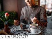 Woman eating delicious chocolate cake in cafe. Стоковое фото, фотограф Tryapitsyn Sergiy / Фотобанк Лори