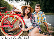 Купить «Love couple with vintage bikes sitting on roadside», фото № 30567833, снято 20 августа 2017 г. (c) Tryapitsyn Sergiy / Фотобанк Лори