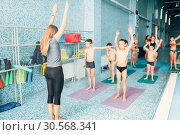 Instructor and group of children doing exercises. Стоковое фото, фотограф Tryapitsyn Sergiy / Фотобанк Лори