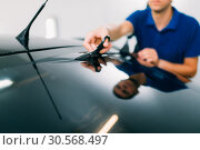 Купить «Worker with scissors, car tinting installation», фото № 30568497, снято 20 сентября 2017 г. (c) Tryapitsyn Sergiy / Фотобанк Лори