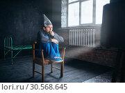 Afraid man in tinfoil helmet watches TV. Стоковое фото, фотограф Tryapitsyn Sergiy / Фотобанк Лори