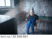 Strange man in aluminum foil helmet watch TV, UFO. Стоковое фото, фотограф Tryapitsyn Sergiy / Фотобанк Лори
