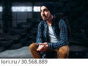Male stalker, traveler against mountain of tires. Стоковое фото, фотограф Tryapitsyn Sergiy / Фотобанк Лори