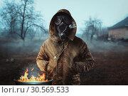 Купить «Stalker soldier in gas mask against fire, doomsday», фото № 30569533, снято 6 декабря 2017 г. (c) Tryapitsyn Sergiy / Фотобанк Лори
