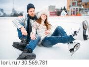 Love couple in skates sitting on ice, skating rink. Стоковое фото, фотограф Tryapitsyn Sergiy / Фотобанк Лори