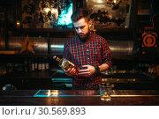 Купить «One man standing at the bar counter, drunkenness», фото № 30569893, снято 20 декабря 2017 г. (c) Tryapitsyn Sergiy / Фотобанк Лори